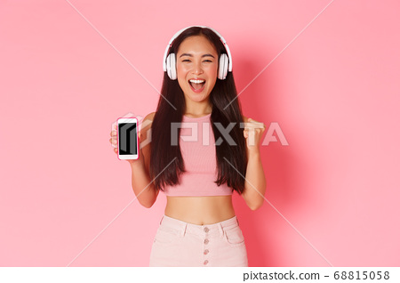 Technology, communication and online lifestyle concept. Gorgeous dancing asian girl looking upbeat, rejoicing as listening music in headphones, showing smartphone screen, pink background 68815058