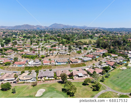 Aerial view of residential neighborhood surrounded by golf in green valley 68817532