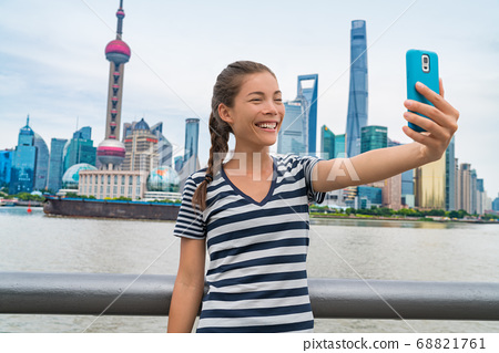 China travel Asian girl tourist taking phone selfie photo on the Bund in Shanghai city vacation. Happy chinese young woman using smartphone app vlogging posting on social media. Multiracial person. 68821761