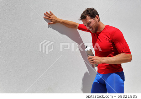 Tired exhausted dehydrated man runner drinking water bottle after workout. Running person taking a break after run. Fitness athlete breathing from sun or heat stroke in summer outdoor training. 68821885
