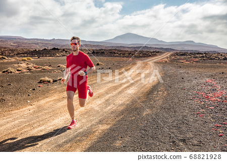 Trail running athlete fitness man runner sprinting on desert dirt road wearing compression clothes and wearable tech smartwatch watch for cardio tracking. Summer outdoor landscape. 68821928