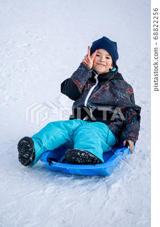 Young Boy Sitting On The Blue Sled on the Snow Mountain 68822256