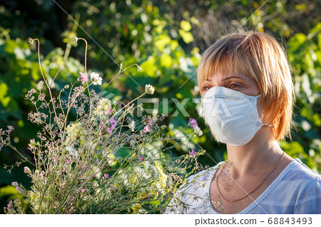 Woman in protection mask holding bouquet of 68843493