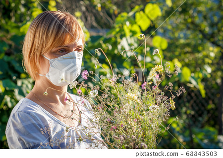 Woman in protection mask holding bouquet of 68843503