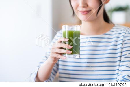 야채 주스를 마시는 젊은 여성 68850795