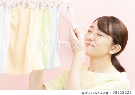 세탁 한 수건으로 미소 짓는 여성 68852828