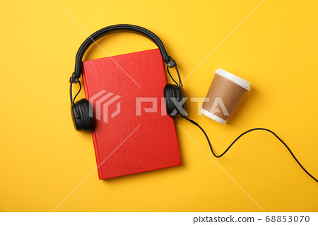 Red book, headphones and coffee cup on yellow 68853070