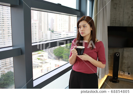 girl with the hot drink near the window 68854805