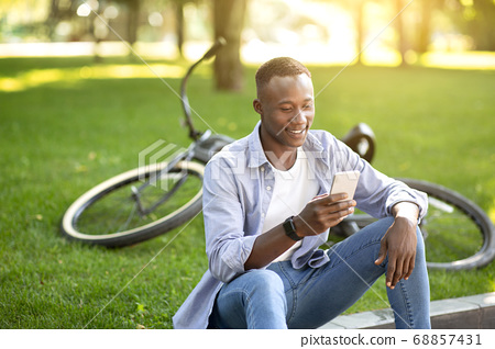 Funky African American man with bicycle browsing internet on his smartphone at urban park 68857431
