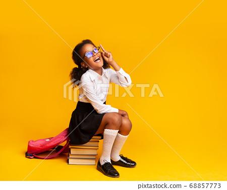 Schoolgirl Having Idea Pointing Finger Up Sitting On Books, Studio 68857773