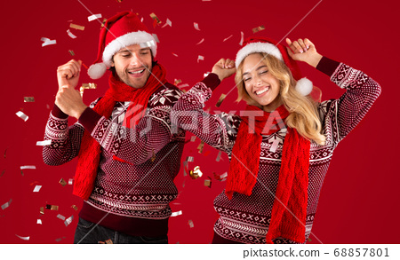 Lovely young couple in sweaters and Santa hats dancing on Christmas or New Year party on red background 68857801
