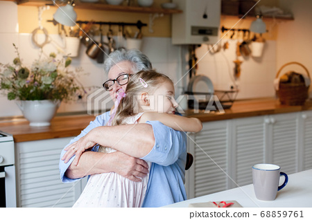 Grandmother hugging child in cozy kitchen at home. Happy family giving thanks. Cute little girl. 68859761