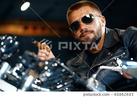 Cool bearded man biker in sunglasses sitting on his motorbike and smoking cigar 68862683