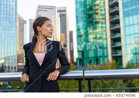 Asian business woman portrait of young female professional businesswoman in suit contemplative outside office buildings. Confident successful multicultural Chinese / Caucasian woman 68874096