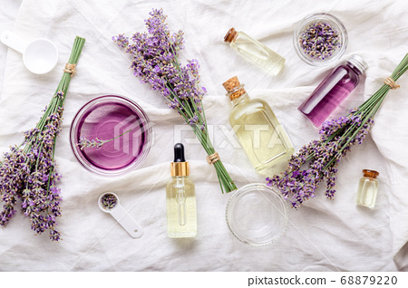Lavender oils serum and lavender flowers on white fabric. Skincare cosmetics products. Set natural spa beauty products. Lavender essential oil, serum, body butter, massage oil, liquid. Flat lay 68879220