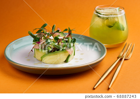 Fresh summer salad of avocado, broccoli and young beans, lime dressing. selective focus, orange background 68887243