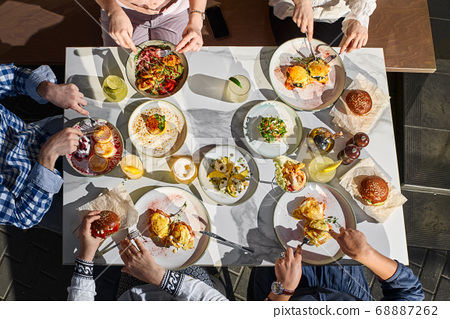 food, eating and family concept - group of people having breakfast and sitting at table 68887262