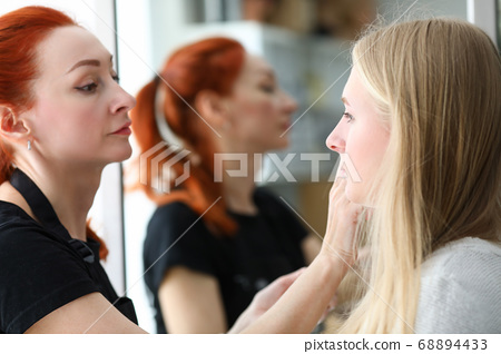 Woman beautician makes makeup in salon blonde girl 68894433