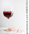 Glass of red wine on table with spilled drink 68895002
