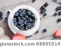 Cup with blueberries near macaroons 68895014