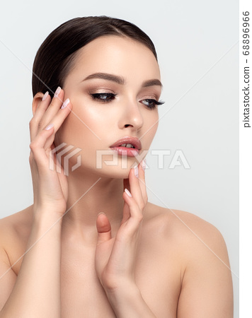 Young beautiful woman touching her face 68896966