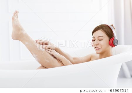 young woman with headphones relaxing in bathtub 68907514