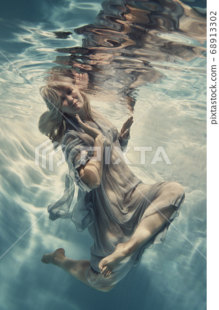 A woman in a blue dress, thin and developing as in weightlessness, floats under water. 68913302