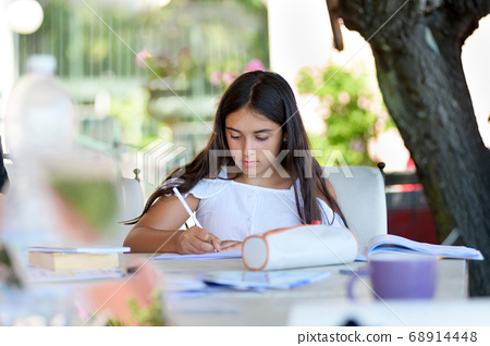 Young girl doing her homework on an outdoor patio 68914448