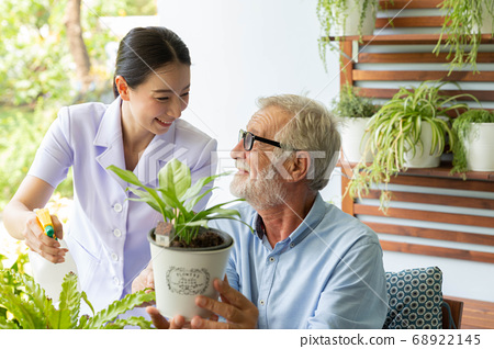 Senior retirement man and nurse are watering a 68922145