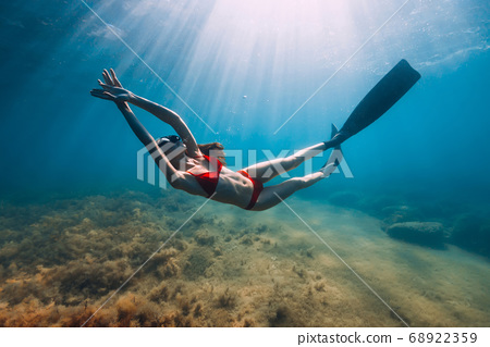 Slim woman in bikini glides at blue sea with sun rays. Freediving with fins underwater in sea 68922359