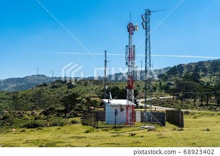 Telecommunication and telephone antenna in green landscape 68923402