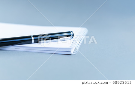 Directly above view of white notepad on blue table. Notebook with the schedule shoot from the top. Spiral notebook blue background. View through bills and home finances 68925613