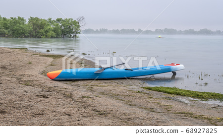 stand up paddleboard on a foggy lake 68927825
