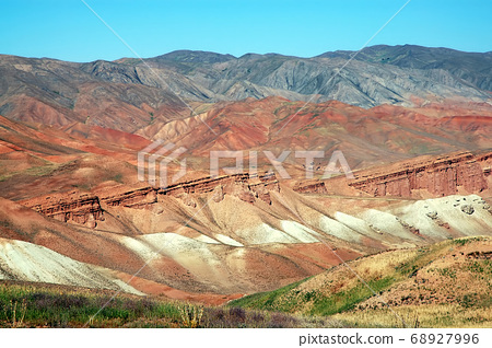 Mountain scenery between Lal and Dowlat Yar in Ghor Province, Afghanistan. These red mountains are at the western end of the Hindu Kush mountain range in Central Afghanistan. Red Afghan mountains. 68927996