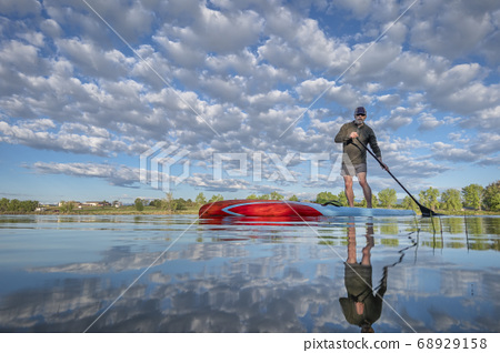 Senior male paddling a stand up paddleboard on a 68929158