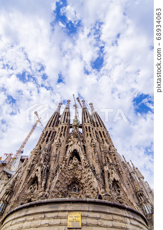 Blue sky, clouds and Sagrada Familia birth facade 68934063