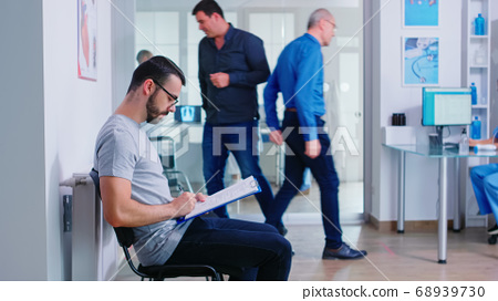 Young man filling documents in hospital waiting area 68939730