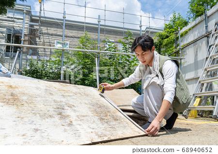 在一個建築工地工作的年輕木匠人 68940652