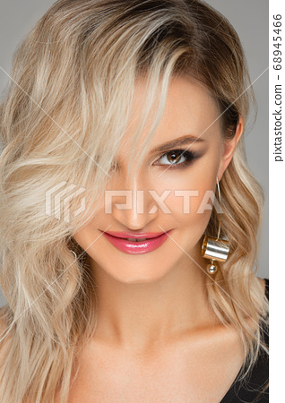 Gorgeous model with make up smiling at camera. 68945466