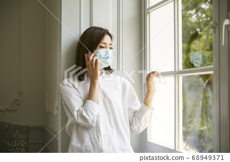 young asian woman in quarantine wearing mask standing by window talking on cellphone looking sad 68949371