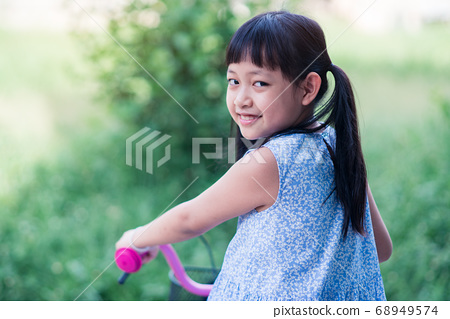 Asian little girl riding her bicycle outside with 68949574