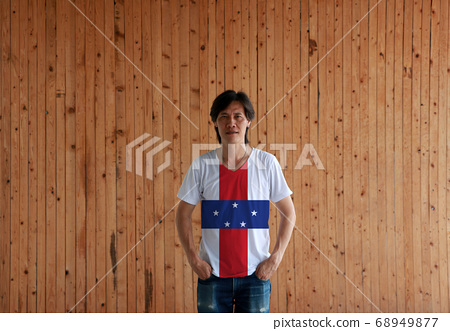 Man wearing Netherlands Antilles flag color shirt and standing with two hands in pant pockets 68949877