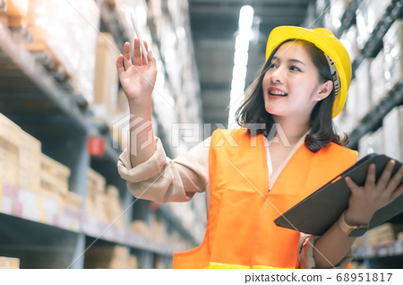 Pretty worker checking stock in the warehouse. 68951817