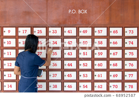 A young woman unlocks mailbox on wall full of mail 68952587