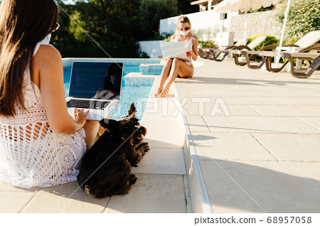 two women using laptops and work remotely in protective face masks 68957058