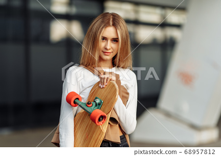 Breast portrait of a beautiful blonde with a skateboard. Lifestyle in the city 68957812
