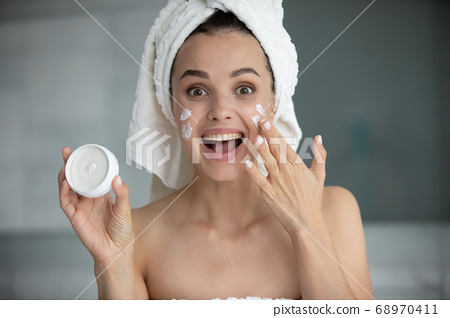 Head shot portrait funny young woman holding face cream jar 68970411