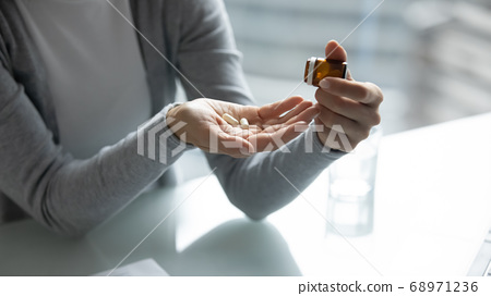 Close up young woman taking out pills from bottle 68971236