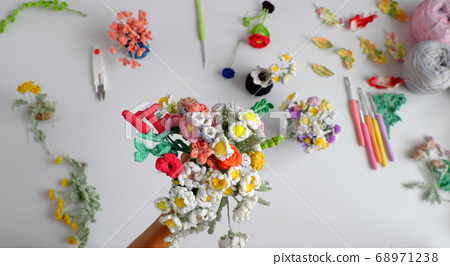 Woman hand hold handmade crochet product, bunch of colorful flower, beautiful artwork diy  in leisure activity  68971238