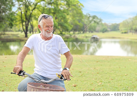 senior man post riding bicycle in the park with clear blue sky (elder healthy concept) 68975809